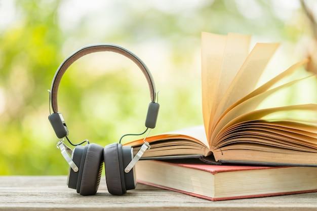 本と抽象的な緑の自然と木製のテーブルに黒のヘッドフォンはぼかします。読書と教育のコンセプト