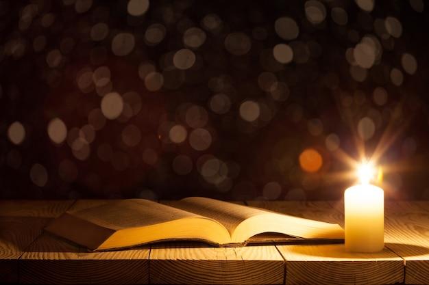 木製の表面に本とキャンドル