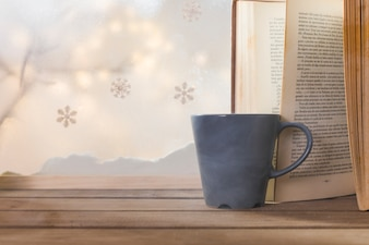 Book and cup on wood table near bank of snow, snowflakes and fairy lights