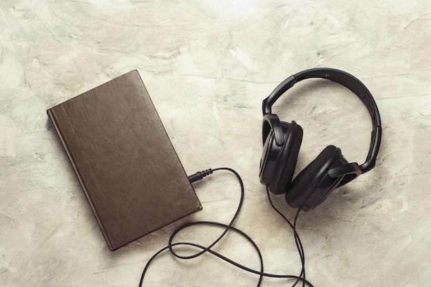 흰 돌에 연결된 책과 헤드폰
