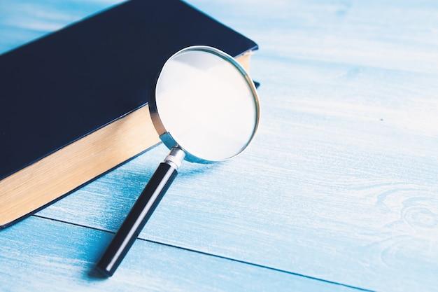 Книга и лупа на столе. концепция поиска и изучения