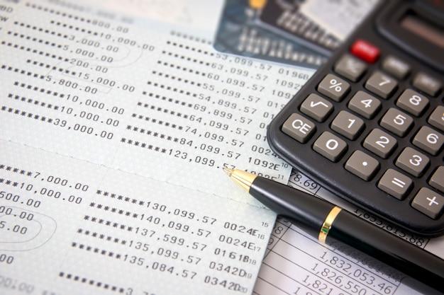 ブックバンク、クレジットカード、電卓、ボールペン。ビジネスファイナンスの概念