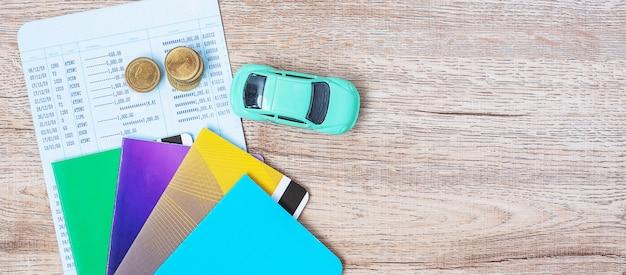 コピースペースの木製テーブルの上の車で本銀行。金融、お金、借り換え、現金と車保険の概念のための車