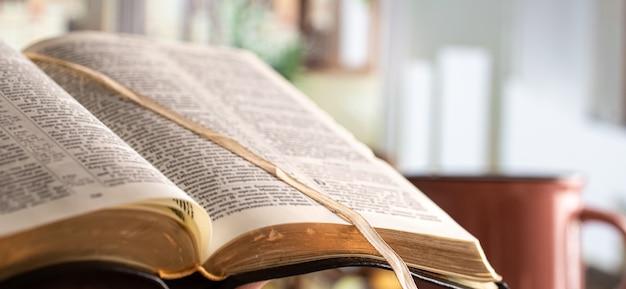 美しいテラスで聖書のクローズアップを予約します。モーニングタイム。テキストのためのスペース。