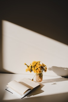 A book and a bunch of yellow dandelions  on the table