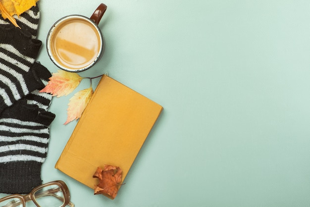 Book, coffee with milk and autumn leaves