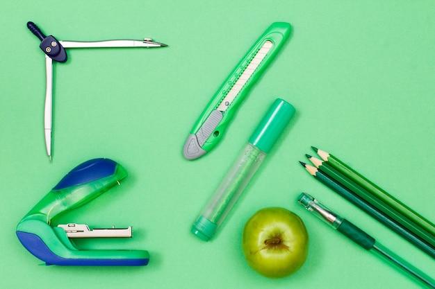 Книга, цветные карандаши, ручка, яблоко, фломастер, нож для бумаги, компас и степлер на зеленом фоне.