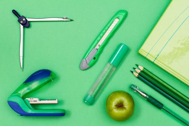 Книга, цветные карандаши, ручка, фломастер, нож для бумаги, компас и степлер на зеленом фоне.