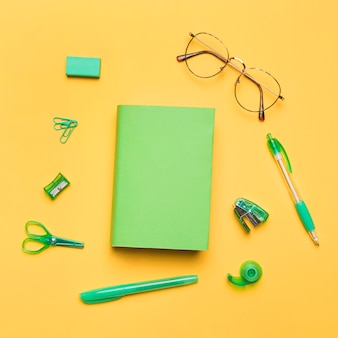 Book in colored cover surrounded by green school supplies