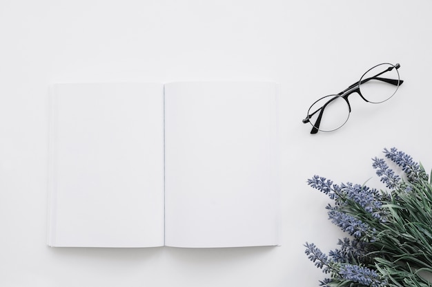 Book cover mockup with glasses and flower decoration
