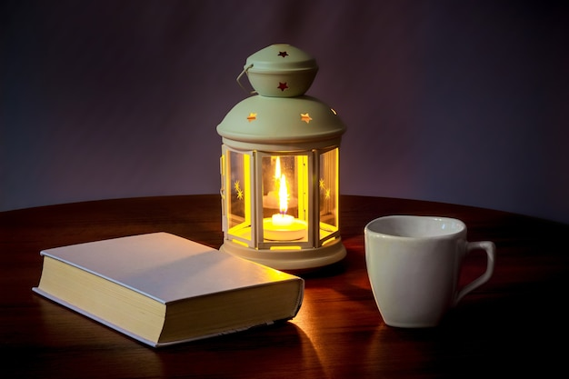 A book and a cup of coffee in the light of a lantern with a candle in the evening