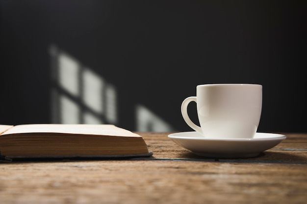 Book and a cup of coffee on a wooden table