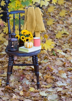 A book, a cup, a pumpkin, next to it is a bouquet of sunflowers and an old lantern in the vase, a knitted yellow sweater