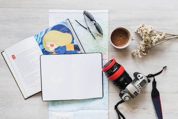Book and diary over the map with personal accessories on desk