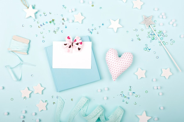 Book and empty card with heart on blue background with stylish decoration stars and sequins. flat lay, top view