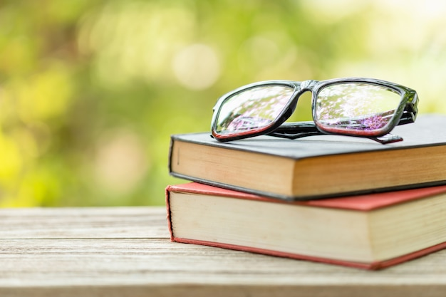 Book and eye glasses on wooden table with abstract green nature blur  reading and education concept