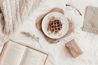 Book, food and other things on bedsheet