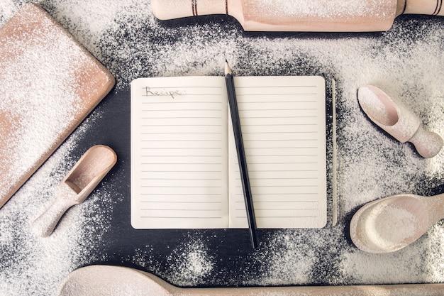 黒の上の道具と小麦粉の周りのレシピの本。上面図。 copyspace。手碑文のレシピ。