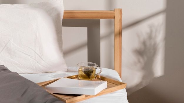 Book and glass of tea on top of the bed