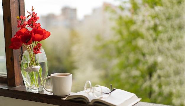책, 안경, 차 한잔과 나무 창에 빨간 튤립