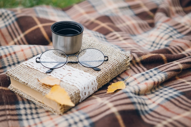 Book, glasses and hot tea from a thermos lie on a blanket