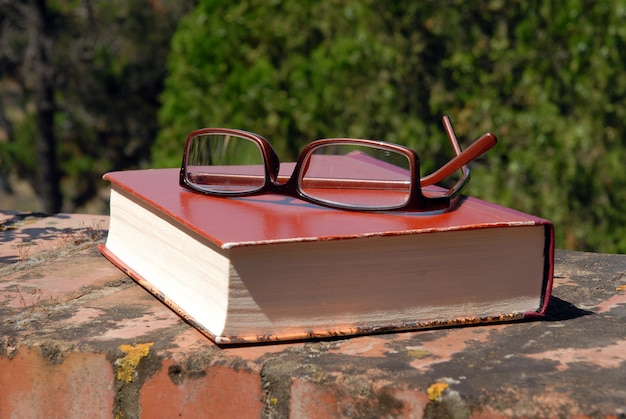 Book and glasses on the wall outdoors