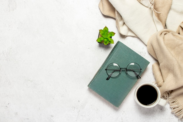 Book, glasses with round glasses, a woolen plaid, a cup with coffee and a flower indoor on a light background.