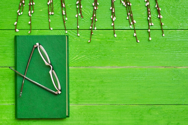 A book in a hard green cover on a green wooden background with glasses and willow branche
