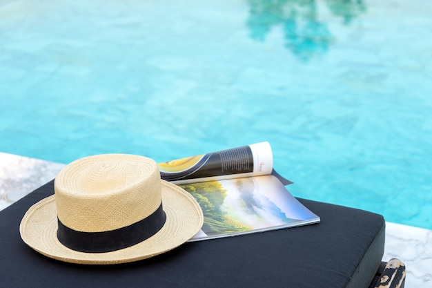 Book and hat on the sun bed near the swimming pool,