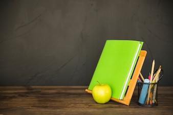 Книжный держатель с канцелярскими принадлежностями и яблоком