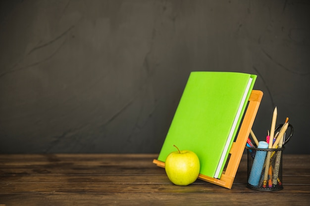 Book holder with stationery and apple
