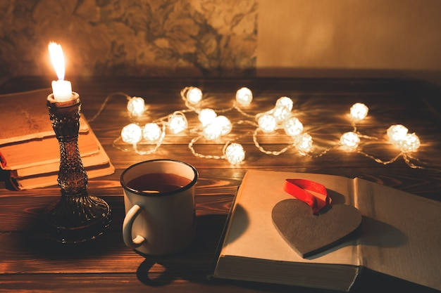 Book and hot tea mug for cosy evening. holidays mood photo with christmas lights. wooden heart and candle. hygge concept. perfect autumn flat lay.