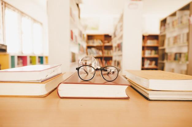 Книга в библиотеке со старым открытым учебником, стопка стопок текстов архива литературы на читальном столе
