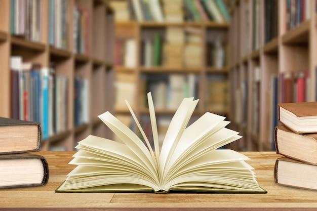 Книга в библиотеке со старым открытым учебником, стопки архивов текстов литературы на столе для чтения,