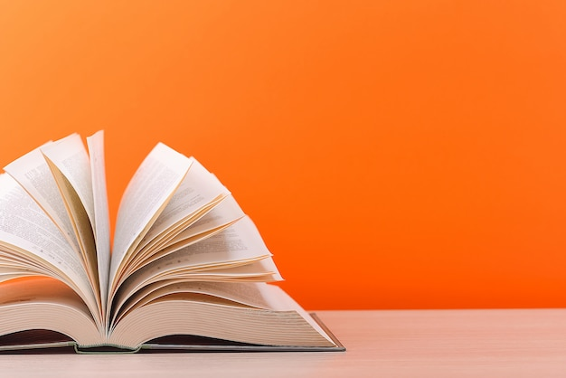The book is open, lying on the table, sheets fanned out on a orange background.