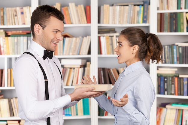 Книга - лучший подарок. веселый молодой ботаник дает книгу красивой молодой женщине, стоя в библиотеке