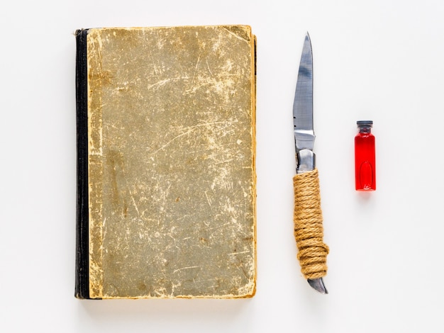 Book, knife and ampoule with blood on a white background. set for magic.