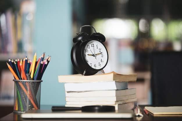 Book, laptop, pencil, clock on wooden table in library, education learning concept