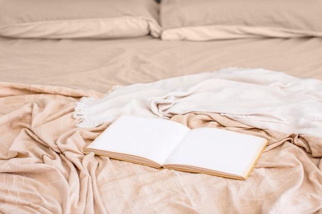 ベッドの上に開いて横たわっている本