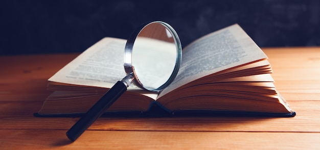 A book and a magnifying glass on the table