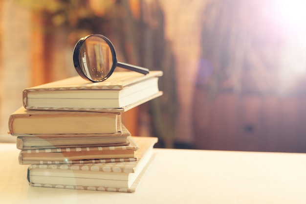 Book and magnifying glass on wooden