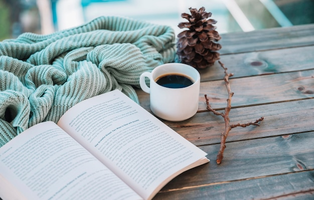 Book near cup and woolen textile on table