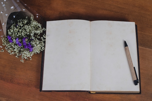Book note with pen on wood table background.