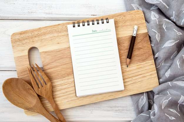 Book notepad paper on a chopping cutting board and tablecloth on white table