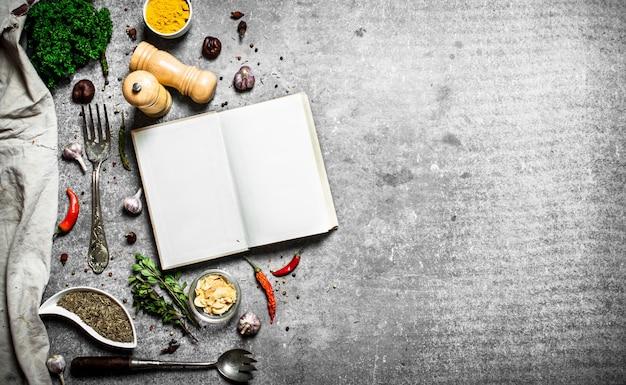 Книга рецептов. свежие специи и зелень. на каменном фоне.
