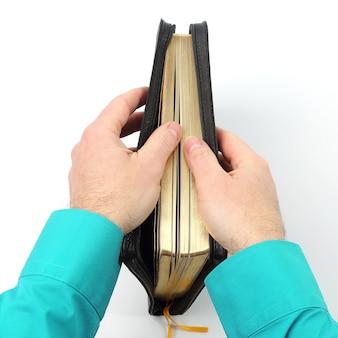 白い背景の上の手で聖書の本