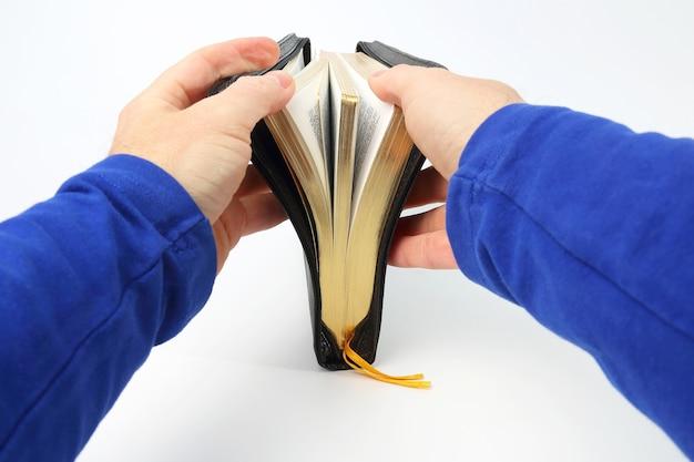 白い表面の手に聖書の本