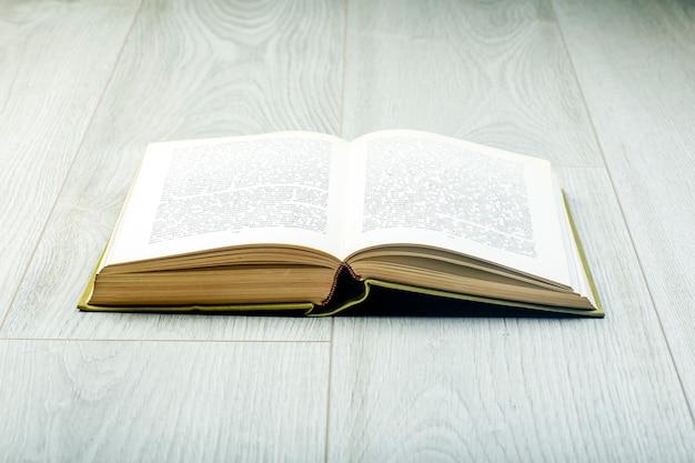 灰色の木製の床で予約します。読書、リラクゼーション、インテリアのコンセプト。