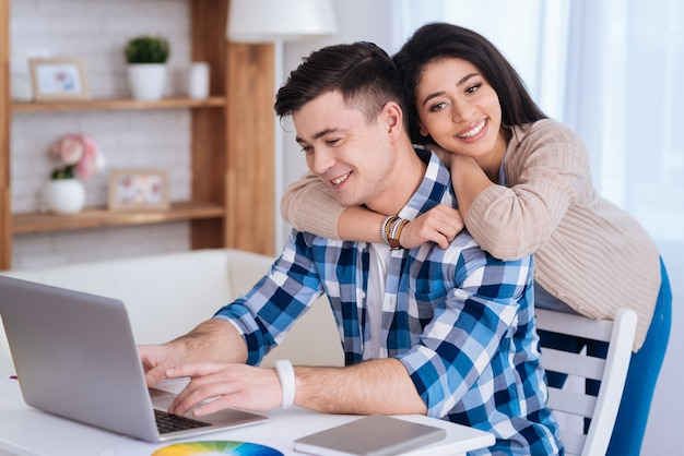 Book online. happy attractive woman hugging man while he using laptop