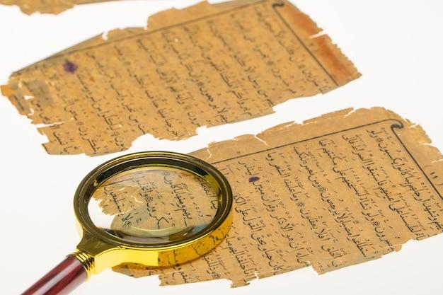 ライトと虫眼鏡のあるテーブルにアラビア語の原稿を載せた本のページ。古書体学、古代アラビア文字の研究